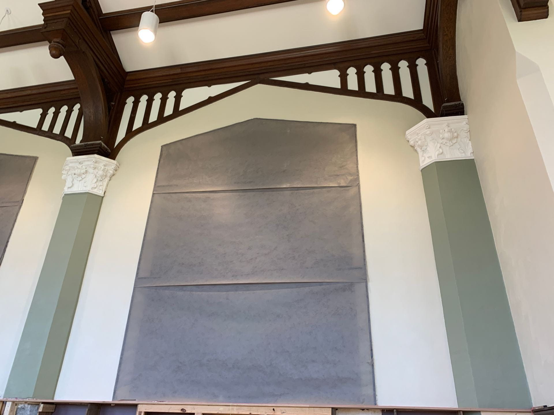 A picture of a Great Room mural, with white cornices, or decorative moldings on either side.