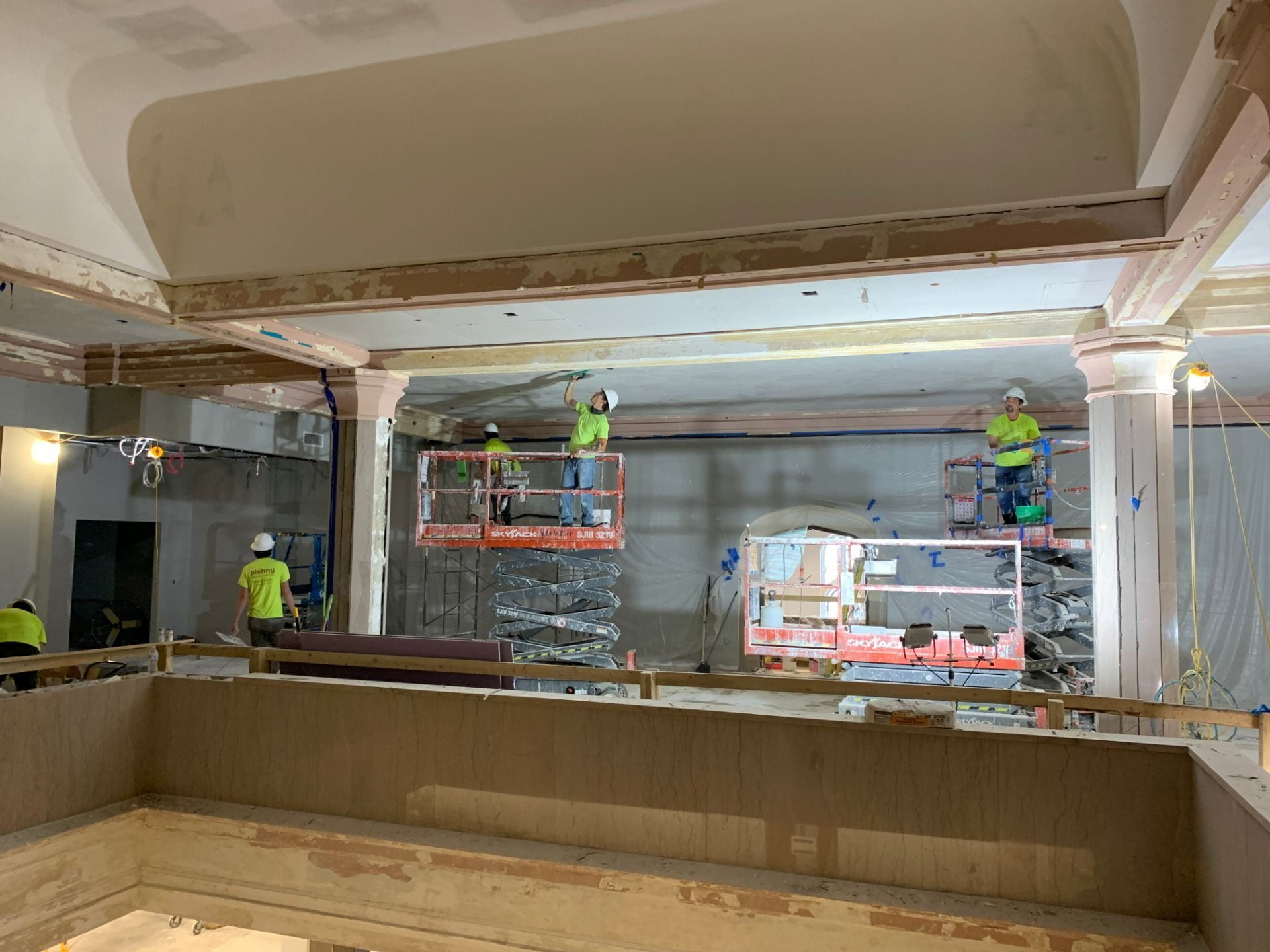 Crew members work on repairing plaster in the fourth floor Academic Learning Center.