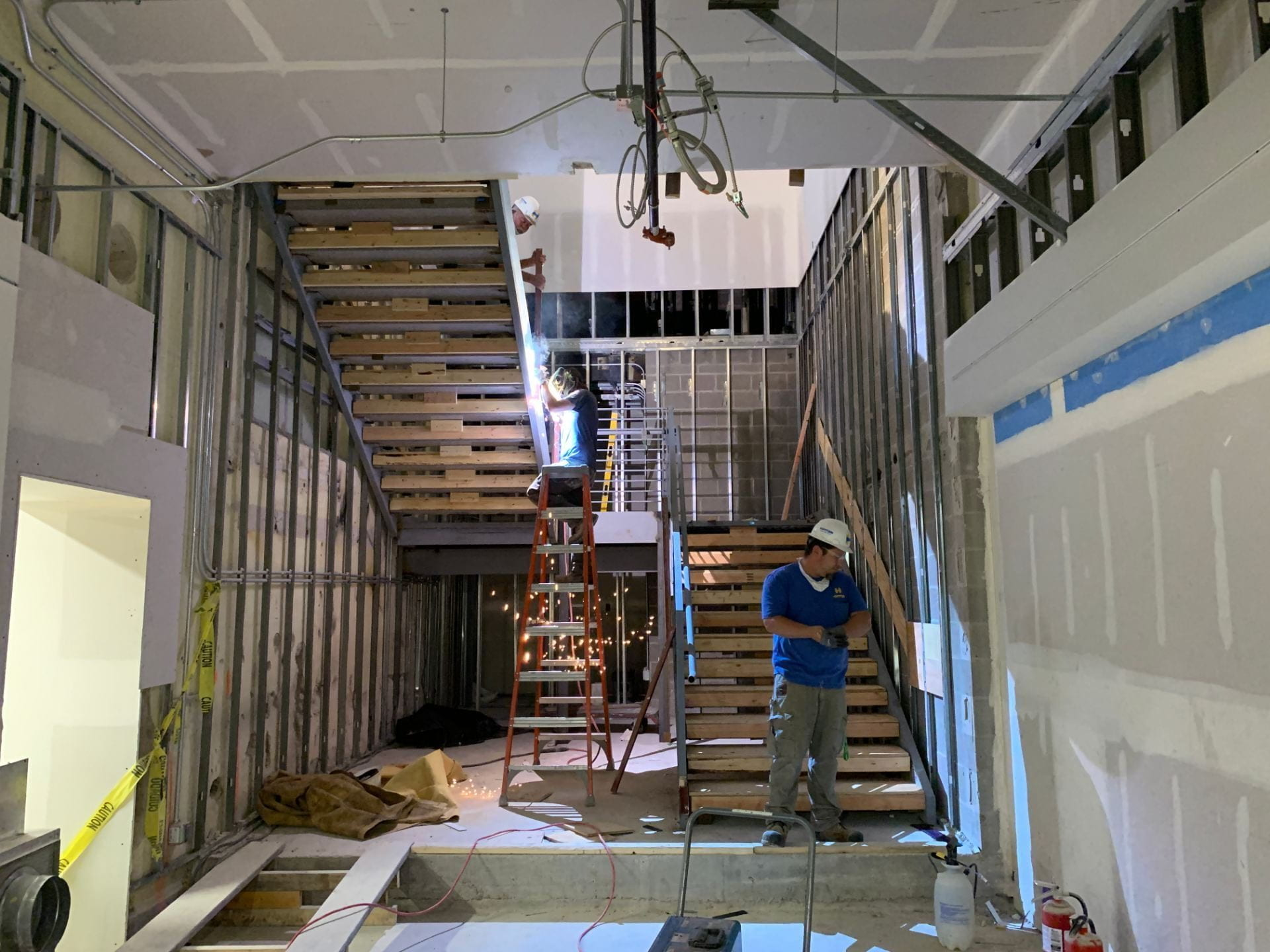 Crew members work on welding the stairs within the Innovation Lab.