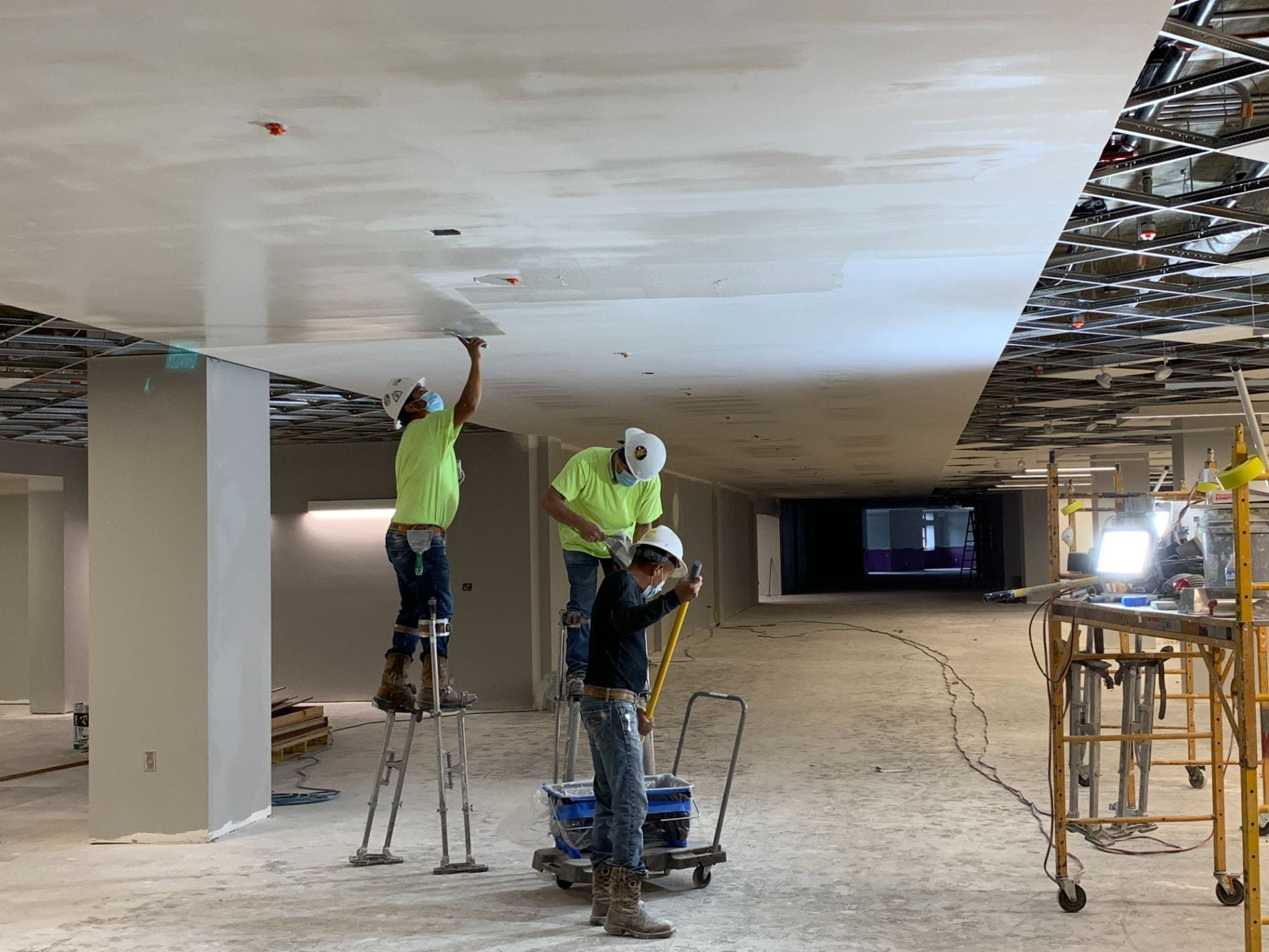 Crew members work on repairing and painting the ceiling in the fourth floor corridor.