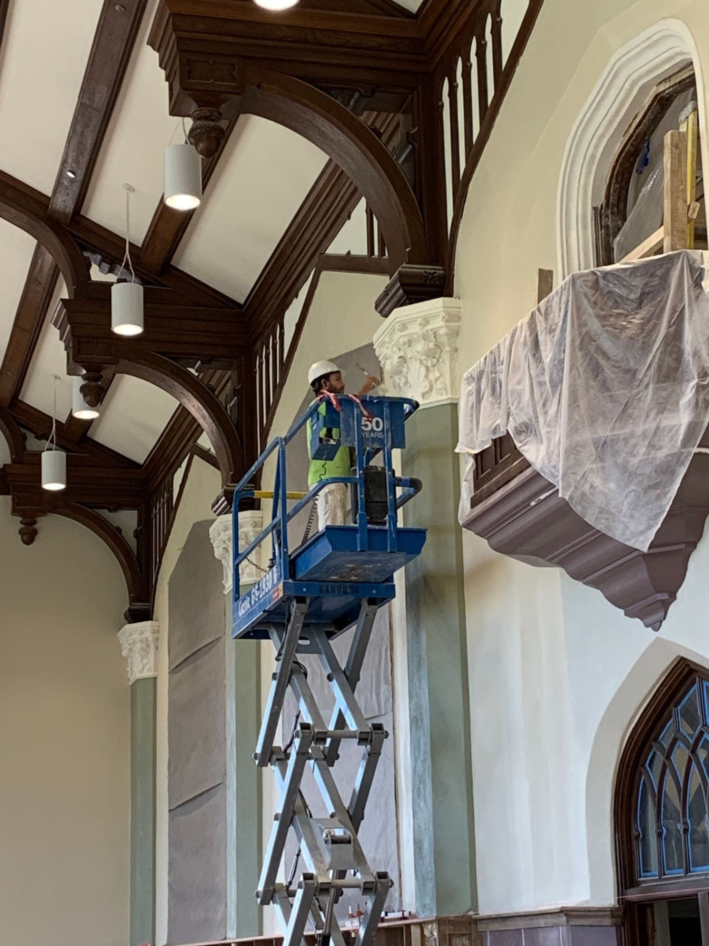 A crew member works on painting the cornices in the Great Room.