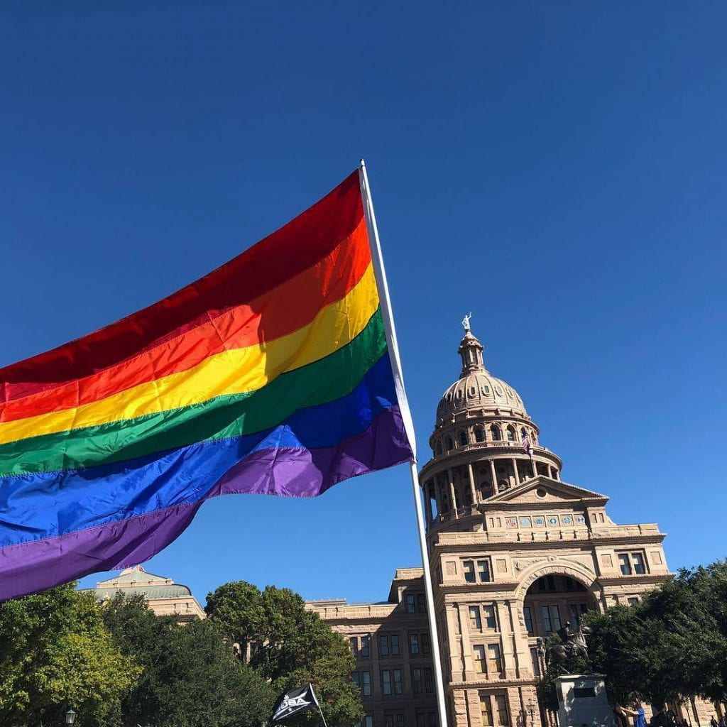 Photo of rainbow pride flag in front of the Texas state capitol