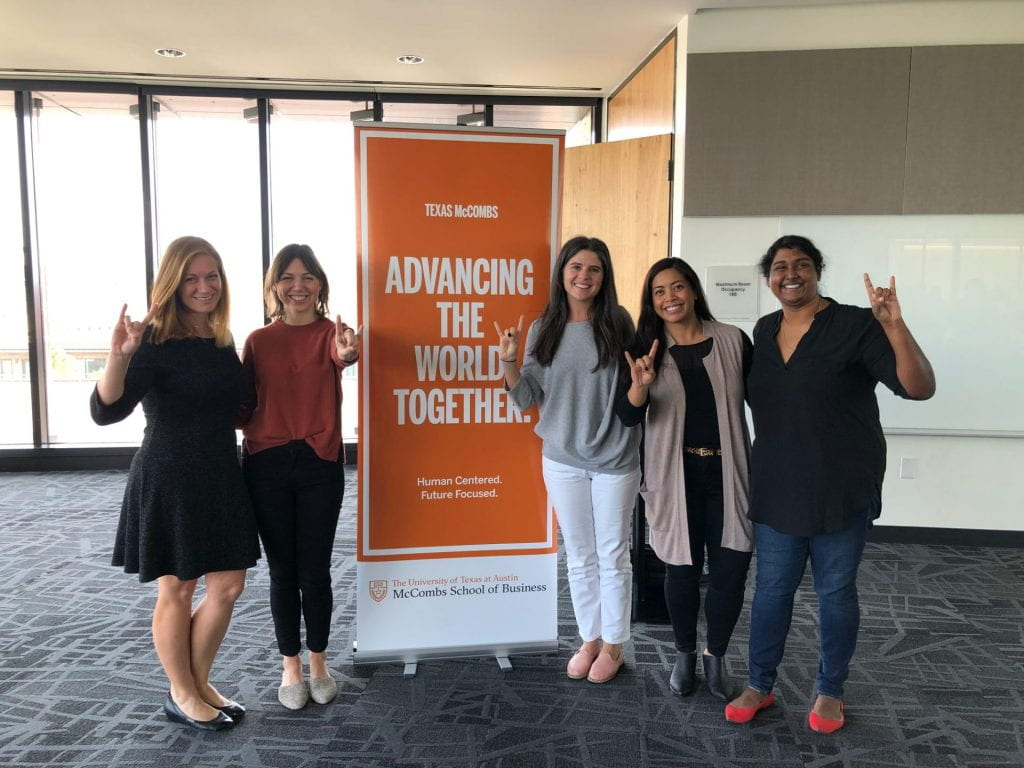 "A picture of The Beyond the MBA Alumni Panel at Discover McCombs: Women's Weekend by a banner that says ""advancing the world together."""