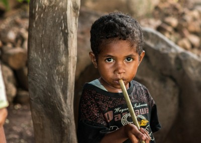A young boy clutches a tube of bamboo to his lips. This is a tube used to spit the seeds of the Kapok tree during a children's game