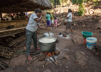 Women stir rice and water in big pots over a wood fire to make ceremonial rice cones in preparation for the Tifoltol feast