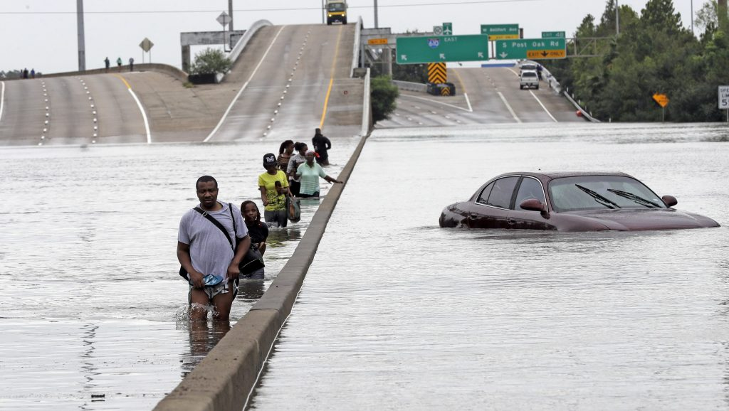 A group of citizens walking through a flooded interstate in Texas during Hurricane Harvey.