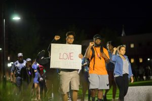 "PC students walk in solidarity around campus holding signs that say ""spread love not hate."""