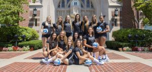 Women's Volleyball poses in front of Harkin's Hall
