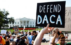 "Protestor holding sign reading ""defend DACA"""