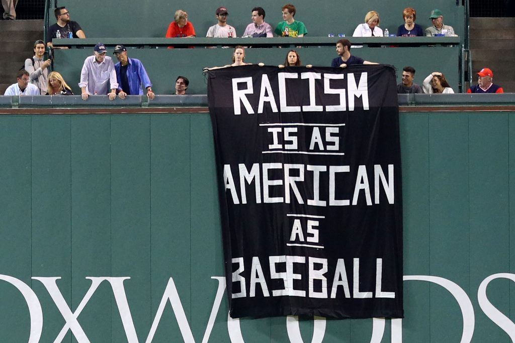 "Protestors display their anti-racism banner in Fenway Park last Wednesday, Sept. 13. The banner reads: ""Racism is as American as baseball."""