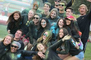 A photo of Board of Programmers members smiling and covered in colored powder