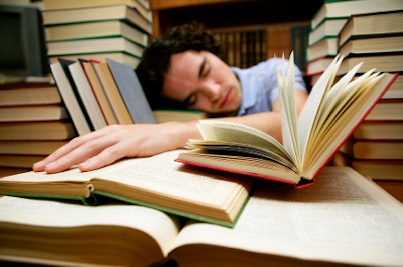 Student falling asleep while studying in the library.