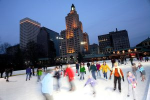 The city lights of Providence serve as a backdrop for ice skaters at the Alex and Ani Skating Rink