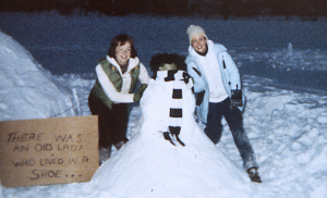 Two woman build a snowman during a storm on Providence College's campus