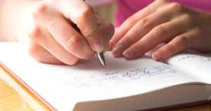 person writing in a diary