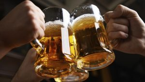 hands clinking beer mugs