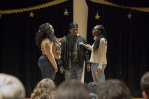 Phionna Cayola Claude '18 (left), Kingsley Metelus '21 (middle), and Sara Jean-Francois '19 preform their poem on stage.