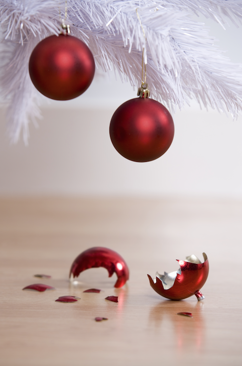 two red orb ornaments dangle precariously from a bottom branch of a christmas tree; on the ground lies a broken ornament