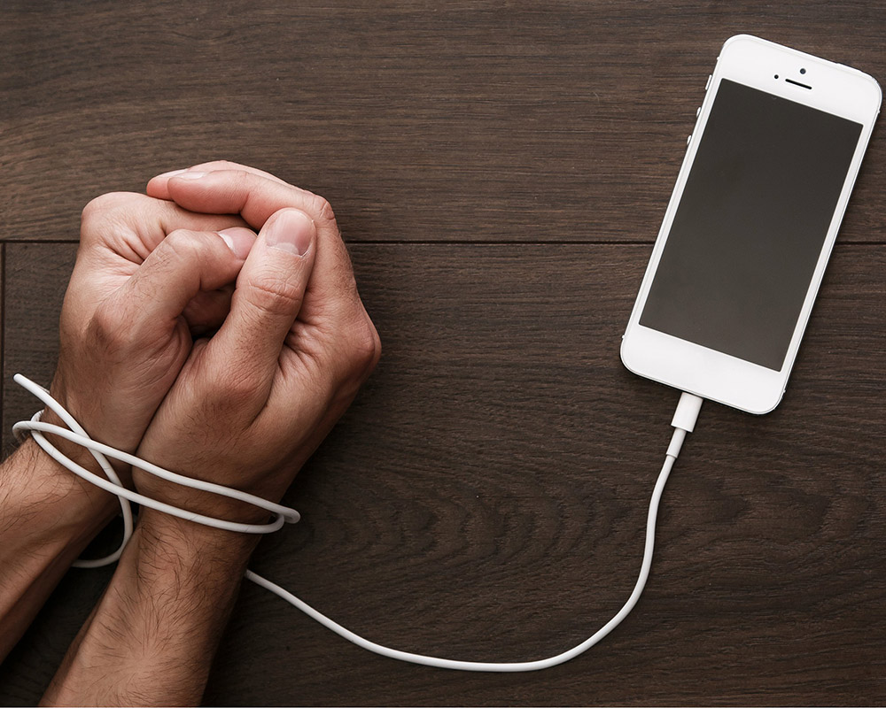 hands bound by iPhone cord