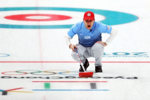 John Shuster of the USA curling team finishes a sweep during the gold medal round.