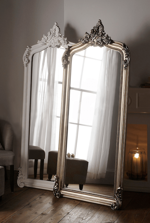 two full-length mirrors leaning against a wall with a fireplace