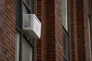 Photo of an air conditioning unit in a window of Aquinas Hall.