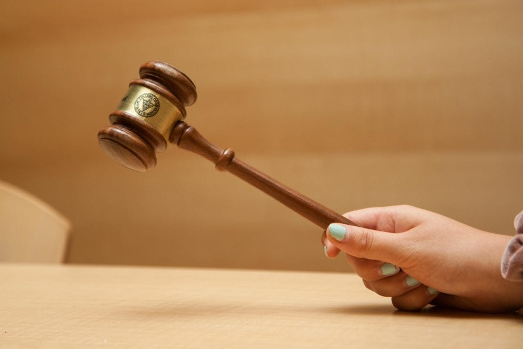 A hand holding a gavel over a table.