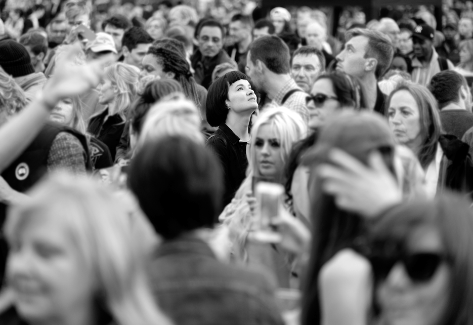 woman stands out in a blurry crowd, looking up