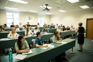 Photo of students taking notes during a lecture.