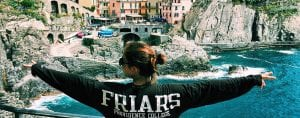 Photo of girl wearing Friars shirt while posing for a picture abroad.