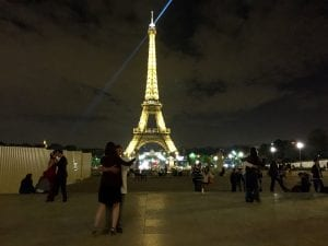 People dancing in front of the Eiffel Tower at night