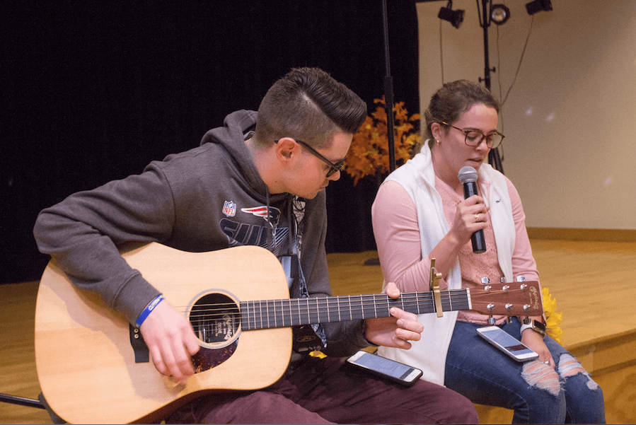 Photo of two students sitting on a stage and performing with a guitar.