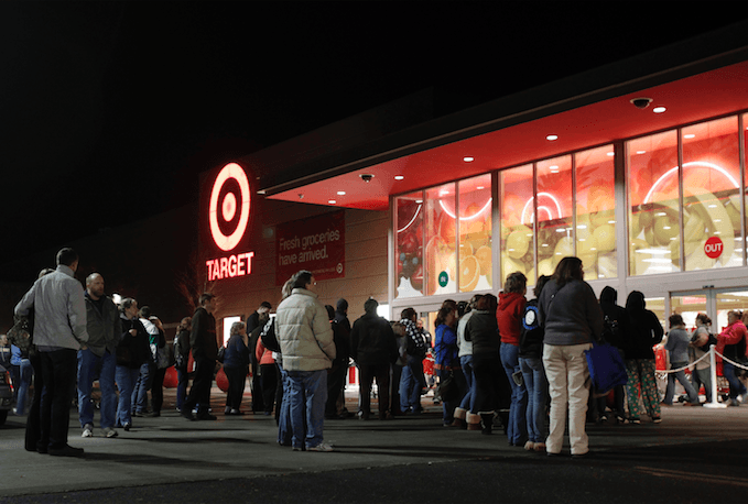 Photo of a long line of people standing outside Target at night.