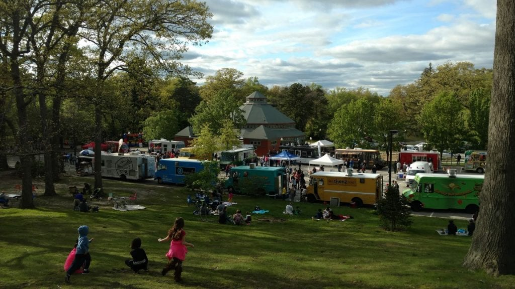 Photo of food trucks at the Roger Williams Zoo with people in the park.