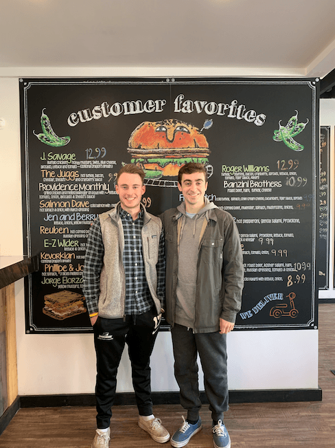 Two students standing in front of a deli menu.