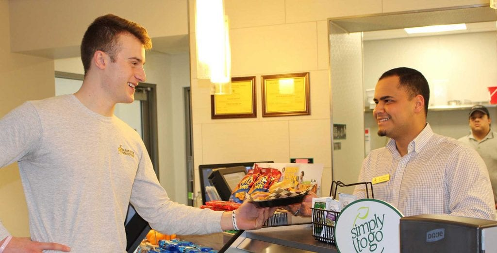 Student buying food at campus cafe.