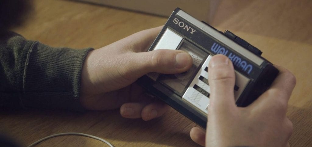 A person listening to and looking at his Walkman