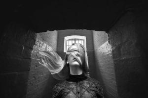 A woman blindfolded by her hair trapped in a jail cell