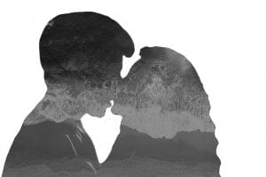 A woman and a man kissing with the ocean filling up their outlines