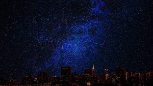 A starry night with a well lit skyline