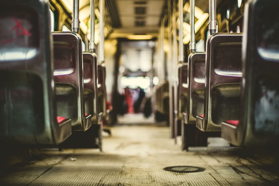 A creative shot of an aisle on a bus with seats on both sides of the photo