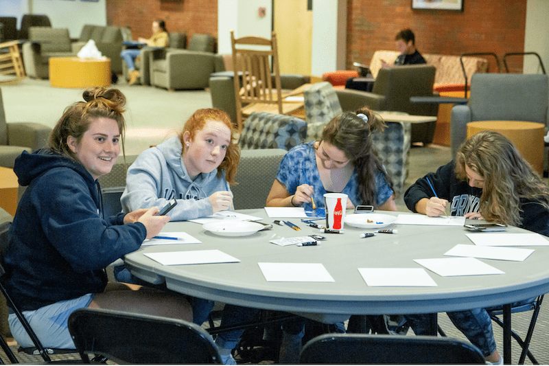 Students make semicolons at a round table in Slavin
