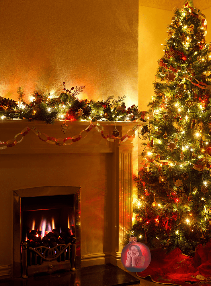 A scene of a Christmas tree full decorated in a family' living room with the reflection of a smiling girl in one of the ornaments