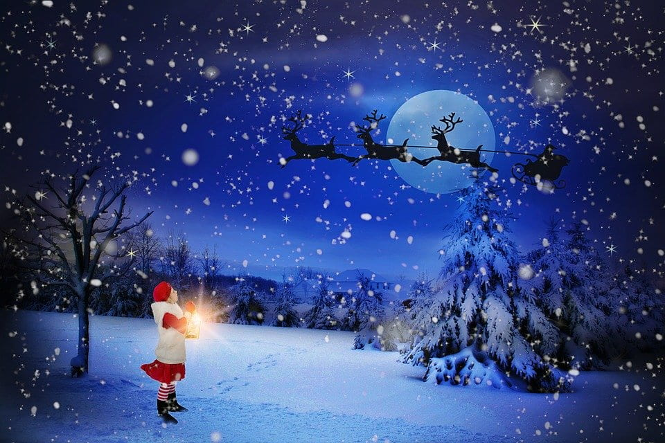 Girl staring up at Santa riding in the wintery night sky on his sleigh