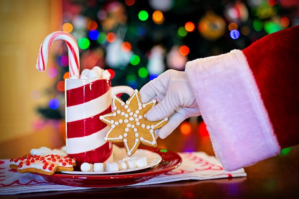 Santa reaching over a plate and grabbing a cookie