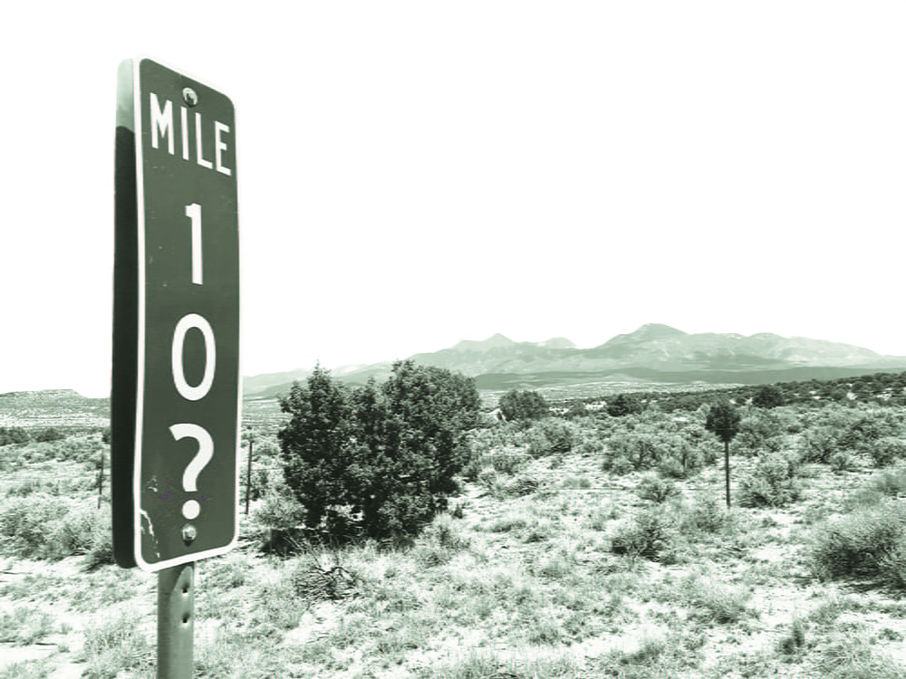 A mile marker that reads 10? in the middle of a desert