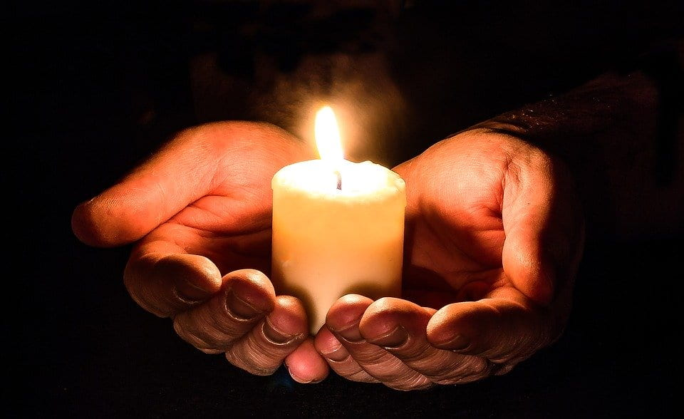 Hands holding a little candle that is lit