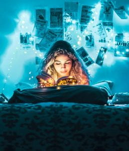 Woman reading a book in her bedroom under the blue tinge of string lights surrounding the room