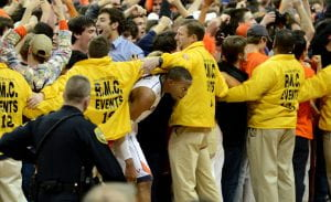 Security holds back fans from running onto the court.