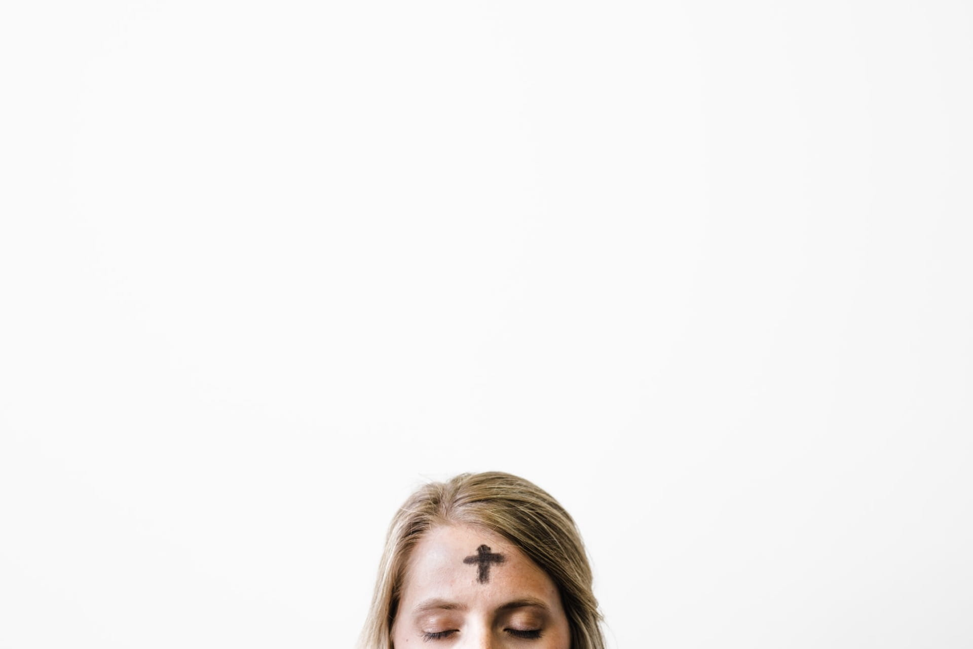 A woman with her eyes closed with ashes on her forehead to celebrate Ash Wednesday